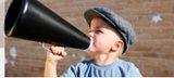 Ein kleiner Junge hält sich ein verhältnismässig grosses Megaphon vor den Mund.